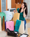 Woman looking purchases and speaking by mobile Stock Image