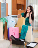Woman looking purchases and speaking by mobile Stock Images