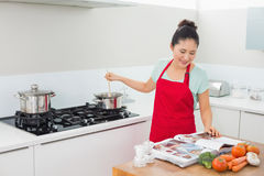 Woman looking at recipe book and preparing food in kitchen Stock Images