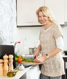 Woman looking recipe  for cooking  in the internet   in home kitchen Stock Photos