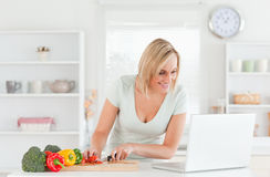 Woman looking for a recipe on laptop. In the kitchen Stock Photos