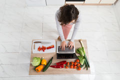 Woman Looking For Recipe On Laptop Stock Photos