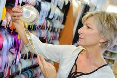 Woman looking at reel ribbon in craft store Royalty Free Stock Photos