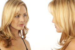 Woman looking at reflection in mirror. Woman looking at her reflection in the mirror Royalty Free Stock Images
