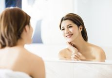 Woman looking on reflection in the mirror at bathroom. Young woman looking on reflection in the mirror at bathroom stock photo