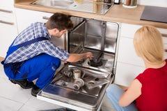 Woman Looking At Repairman Repairing Dishwasher Stock Photo