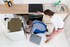 Woman Looking At The Repairman Repairing Dishwasher Royalty Free Stock Images