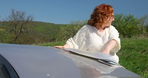 Woman looking for right direction using paper map on bonnet. stock video footage