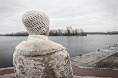 Woman Looking at the River during a Sad Winter Day Stock Photos