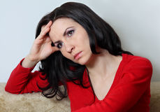 Woman looking sad. Young good looking brunette with long hair sitting supporting her head with hand Royalty Free Stock Photography