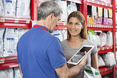 Woman Looking At Salesman Using Digital Tablet In Pet Store. Happy women holding pet food while looking at salesman using digital tablet in store Stock Image