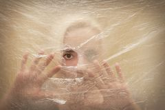 Woman looking scared through hole. In transparent plastic curtain Stock Image