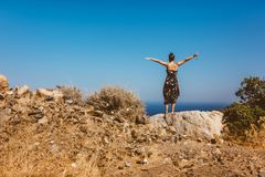 woman looking at sea from the cliffs. Woman in dress enjoying summer and having a carefree holiday Stock Photo