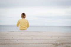 Woman looking through the sea while sitting on beach Stock Photo