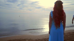 Woman looking at sea sunset. Back view of woman standing on beach at sunset. Red hair woman dreaming on sea beach. Girl in blue dress standing at beach. Woman stock video