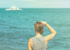 Woman looking at the sea. Toned photo of girl watching cruise boat. Stock Images