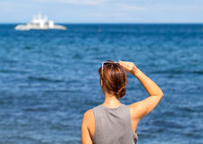 Woman looking at sea. Trendy casual photo of girl watching cruise boat. Royalty Free Stock Images