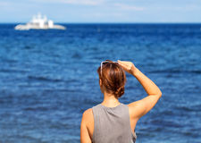 Woman looking at sea. Trendy casual photo of girl watching cruise boat. Stock Photography