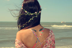 Woman looking at the sea. Woman with a wreath in her hair looking at the sea Stock Images