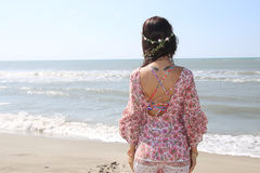 Woman looking at the sea. Woman with a wreath in her hair looking at the sea Stock Photo