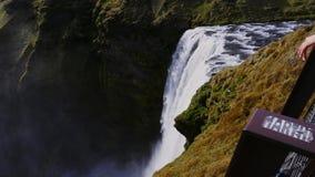 Woman looking at Seljalandsfoss watfall in Iceland. View of Seljalandsfoss watfall in Iceland stock footage