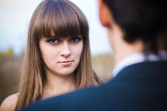 Woman looking seriously over man shoulder Stock Images