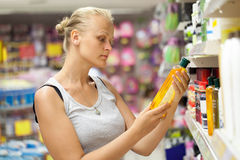 Woman looking at shampoo bottle in the store Royalty Free Stock Photos