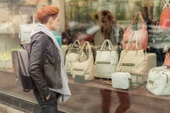 Woman looking in a shop window with handbags Stock Image