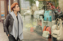 Woman looking in a shop window with handbags Stock Images