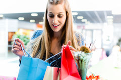 Woman looking into shopping bag in mall Royalty Free Stock Photography