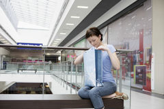 Woman Looking In Shopping Bag At Mall stock photos