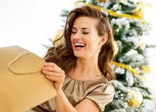 Woman looking into shopping bag near christmas tre Royalty Free Stock Images