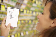 Woman Looking At Shopping List In Supermarket Royalty Free Stock Photos