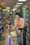 Woman looking at shopping list in supermarket, Beijing Stock Photography