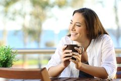 Woman looking at side in an apartment balcony. Happy woman holding a coffee mug looking at side in an apartment balcony Royalty Free Stock Images