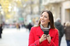 Woman looking at side holding a phone in winter. Happy woman looking at side holding a phone in winter in the street with copy space stock photo