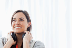 A woman looking slightly upwards and smiling with headphones Royalty Free Stock Images
