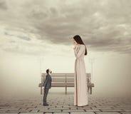 Woman looking at small kissing man Stock Photos