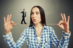 Woman looking at small walking man Stock Photo