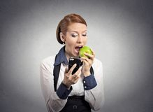 Woman looking at smart phone eating apple. Closeup portrait serious corporate business woman, deal maker reading news on smart mobile phone holding eating green stock photos