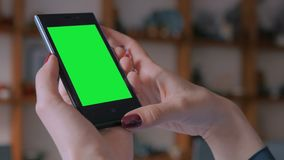 Woman looking at smart phone with greenscreen. Woman looking at vertical smart phone with green screen in pottery workshop, studio. Close up shot of woman hands stock video
