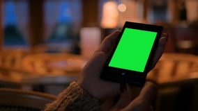 Woman looking at smart phone phone with green screen in cafe stock footage