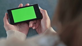 Woman looking at smart phone phone with green screen stock footage