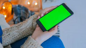 Woman looking at smart phone phone with green screen