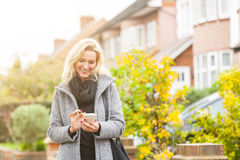 Woman looking at smart phone in residential area of London Stock Photography