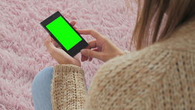 Woman looking at smartphone with green screen. Close up shot of woman's hands with mobile stock video footage