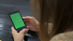 Woman looking at smartphone with green screen. Close up shot of woman's hands with mobile stock footage