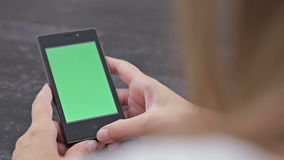Woman looking at smartphone with green screen. Close up shot of woman`s hands with mobile stock video footage