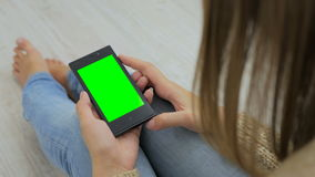 Woman looking at smartphone with green screen. Close up shot of woman`s hands with mobile Stock Image