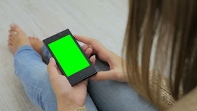 Woman looking at smartphone with green screen. Close up shot of woman`s hands with mobile stock video